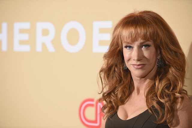 Kathy Griffin posing on a red carpet while wearing a black dress.