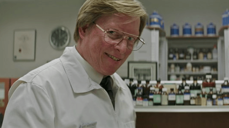 A pharmacist wears glasses and stands in front of a shelf filled with medicine