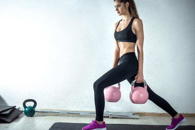 A woman does lunges with kettlebells.