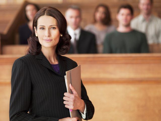 Smiling lawyer holding file in courtroom