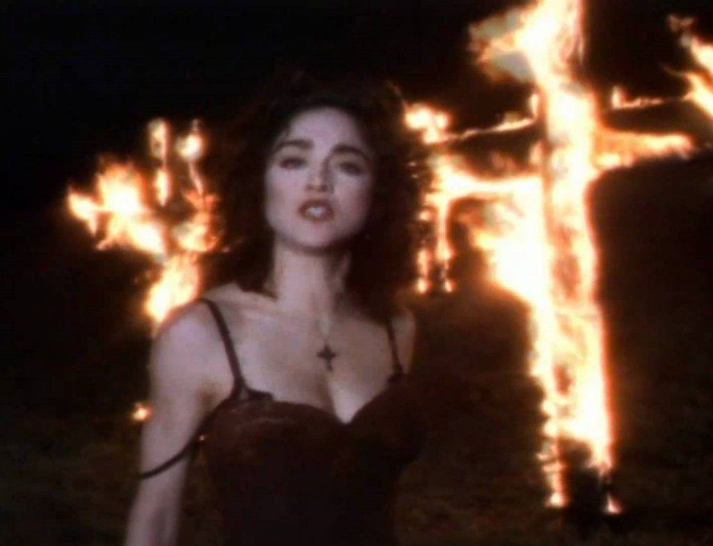 Madonna poses in front of a burning cross in her 'Like a Praye'r video.