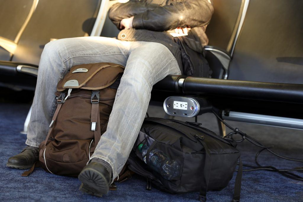 Man sitting in airport with backpacks