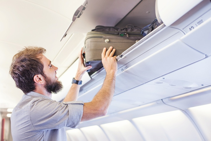 man putting luggage on the top shelf on airplane
