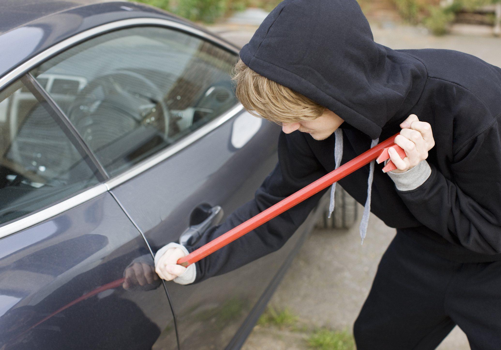 Man in hoodie breaking into car