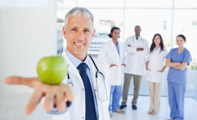 Doctor with an apple and doctors behind him.