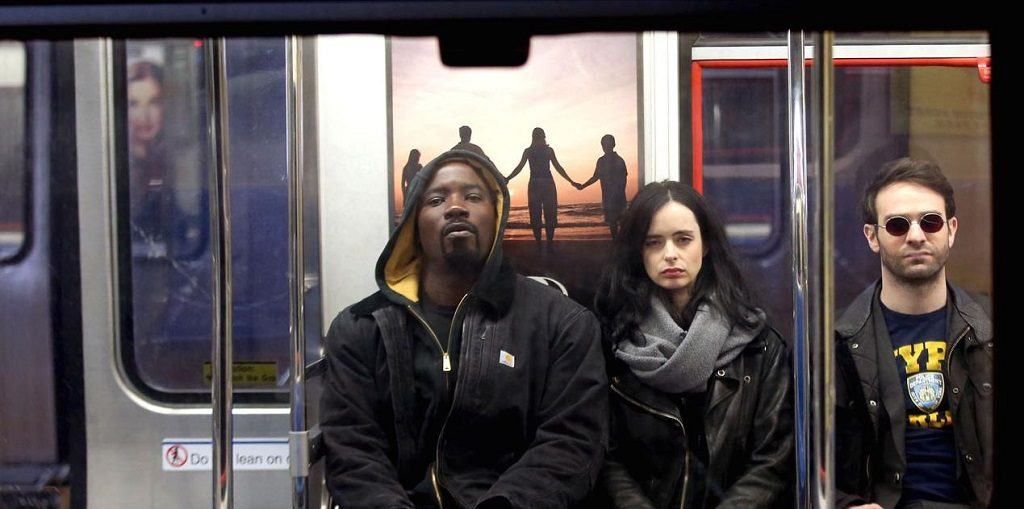 Mike Coulter, Krysten Ritter, and Charlie Cox in Marvel's The Defenders sitting on a subway train