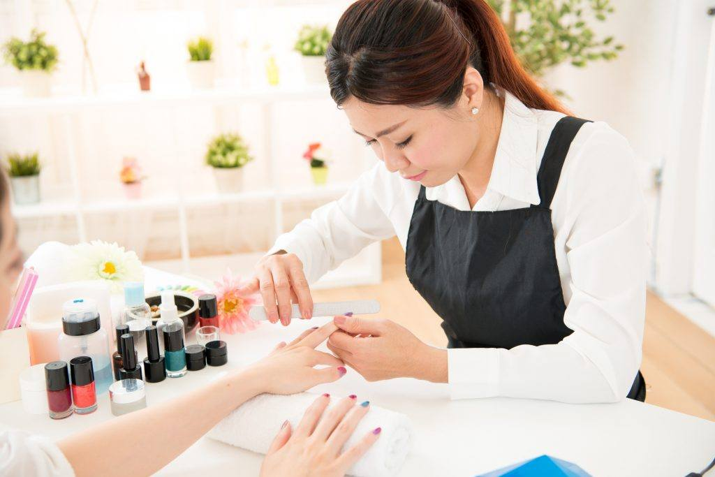 Nail technician performing manicure