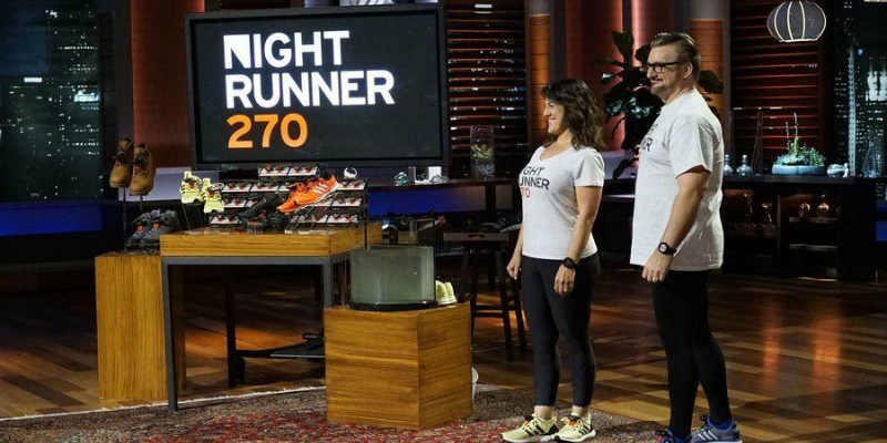 A man and woman stand on the show displaying their sneakers.