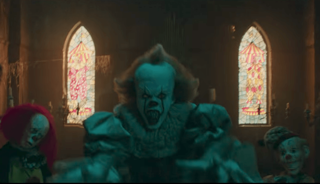 A clown stands in a room full of dolls