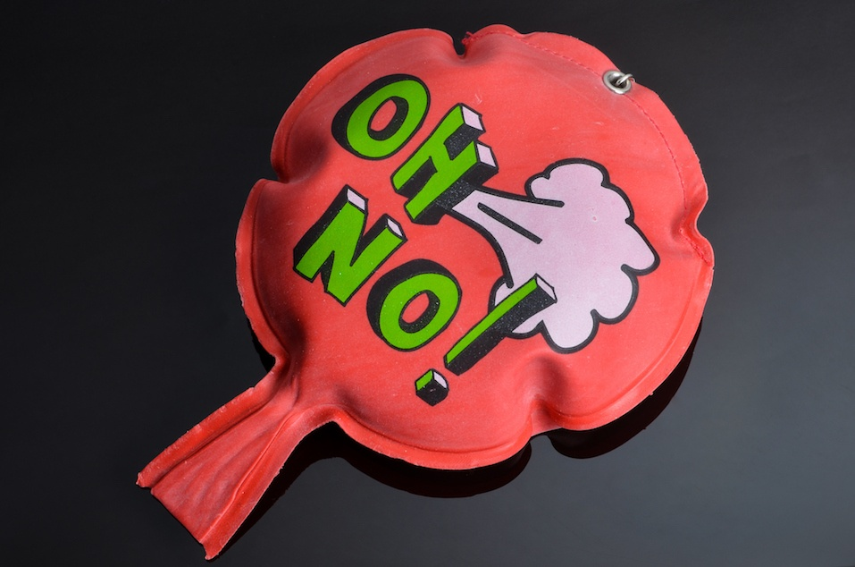 red rubber whoopee cushion with reflection on black glass