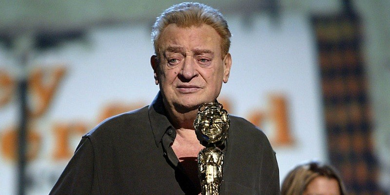 Rodney Dangerfield is on stage with an award.