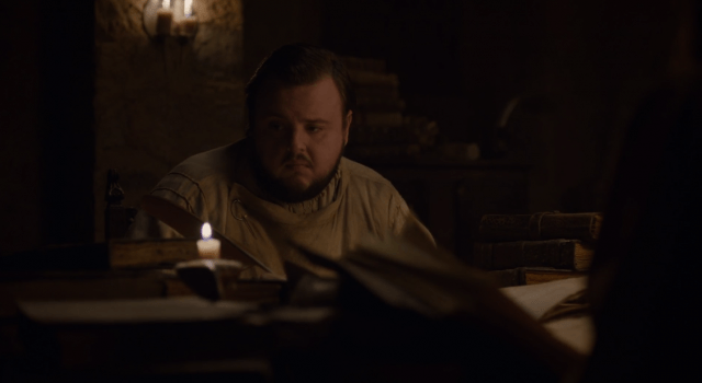 Looking disgruntled, Sam Tarley sits with a quill in his hand and stares at a book.