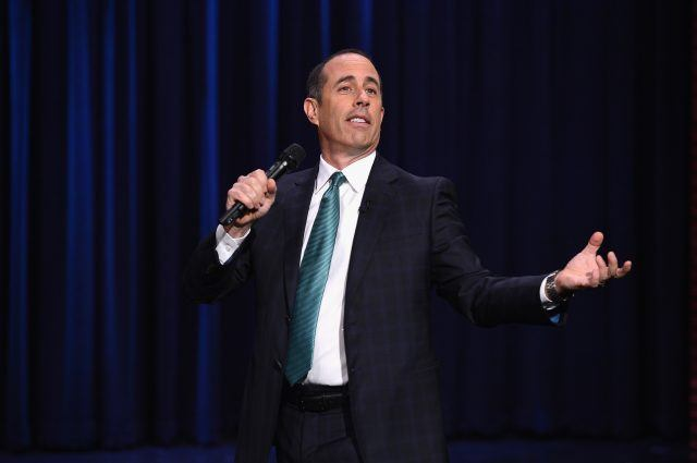 Jerry Seinfeld performing a comedy routine while holding a microphone.