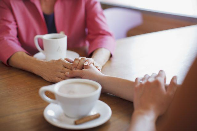 Two people drinking coffee and holding each other's hands.