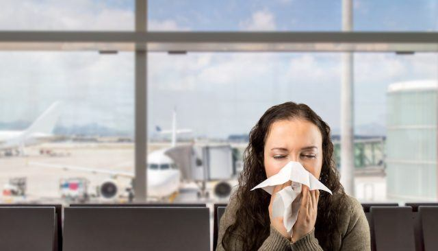sick woman sneezing at the airport