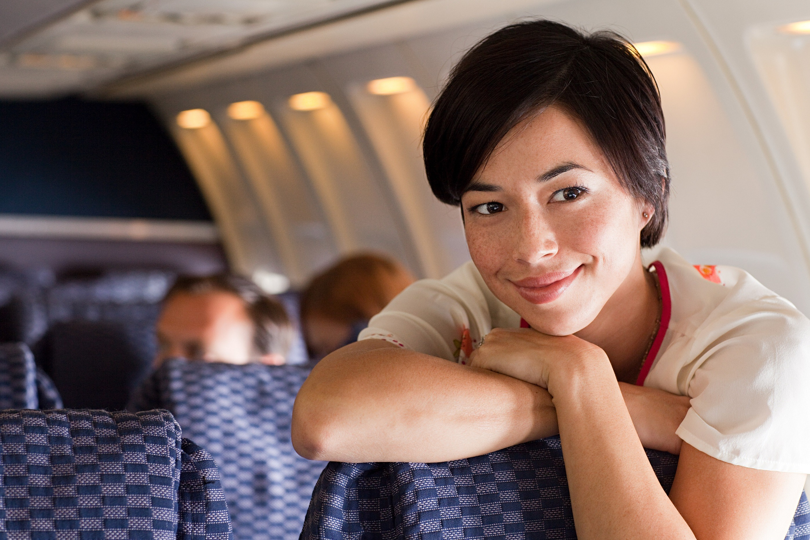 Young woman standing on an airplane