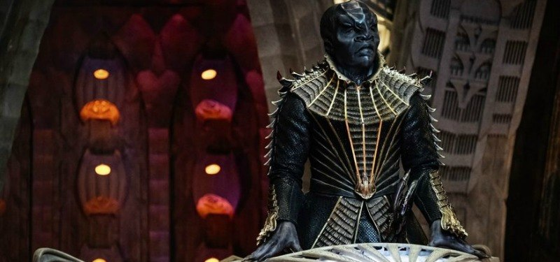 A Klingon stands behind a podium on a ship.