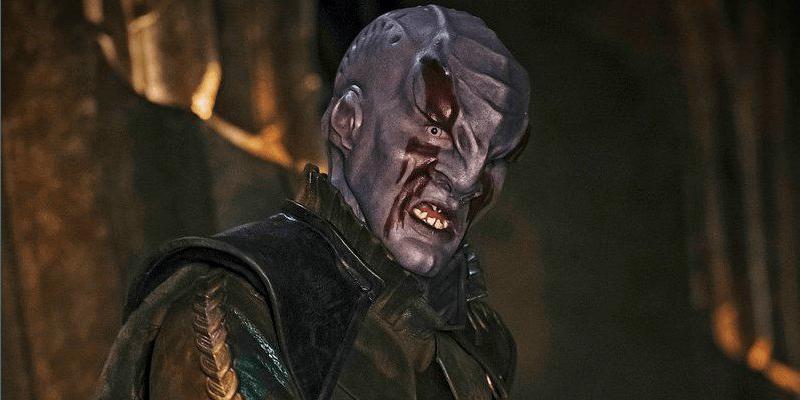 A purple Klingon looks into the camera.