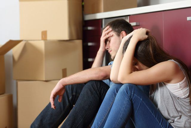 Couple sitting on the floor next to moving boxes looking upset