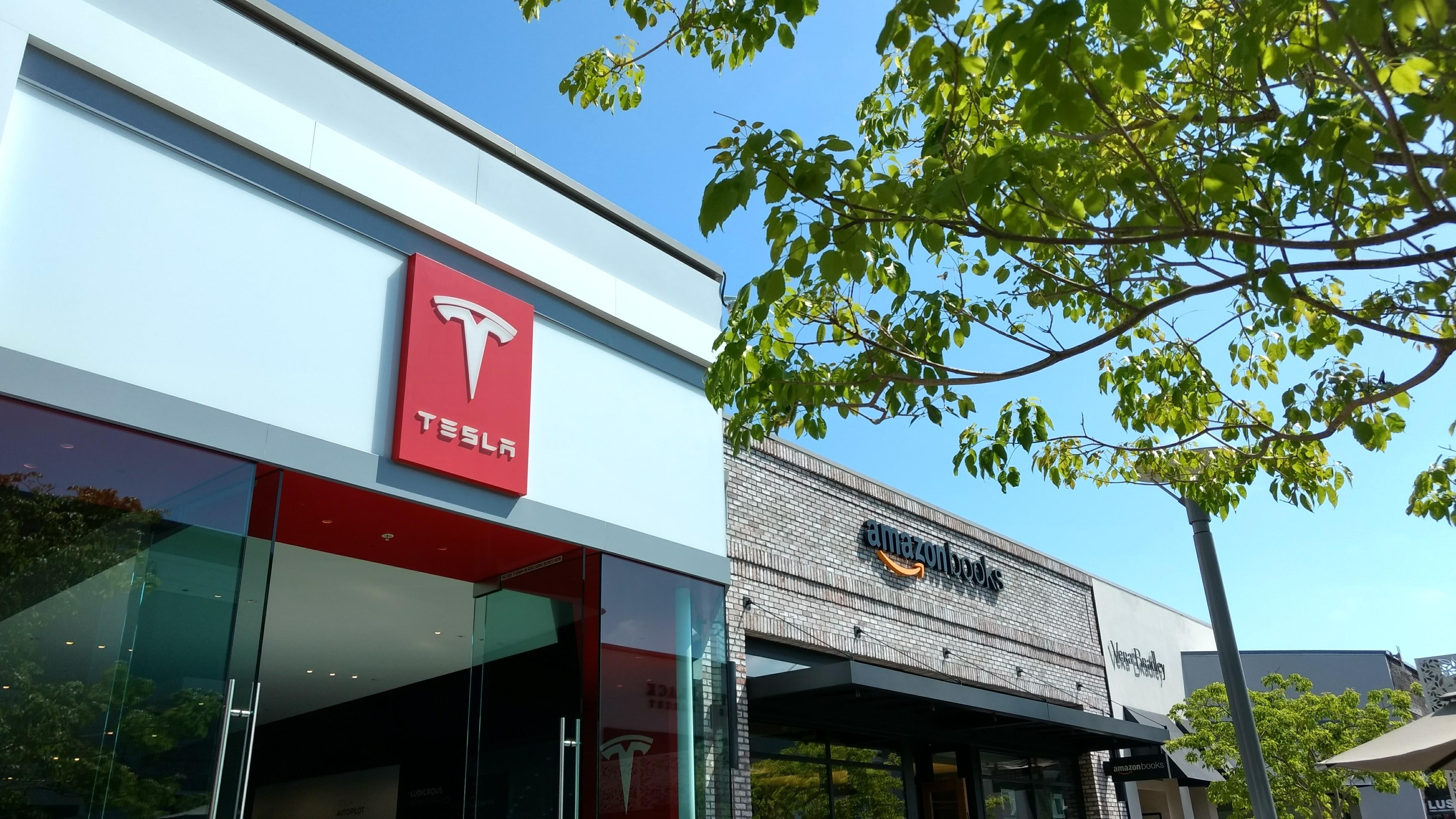 storefronts of Tesla showroom and Amazon bookstore