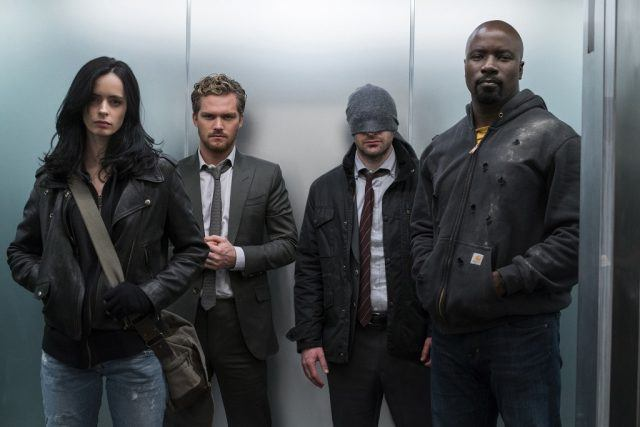 Krysten Ritter, Finn Jones, Charlie Cox, and Mike Coulter in The Defenders standing together in an elevator.
