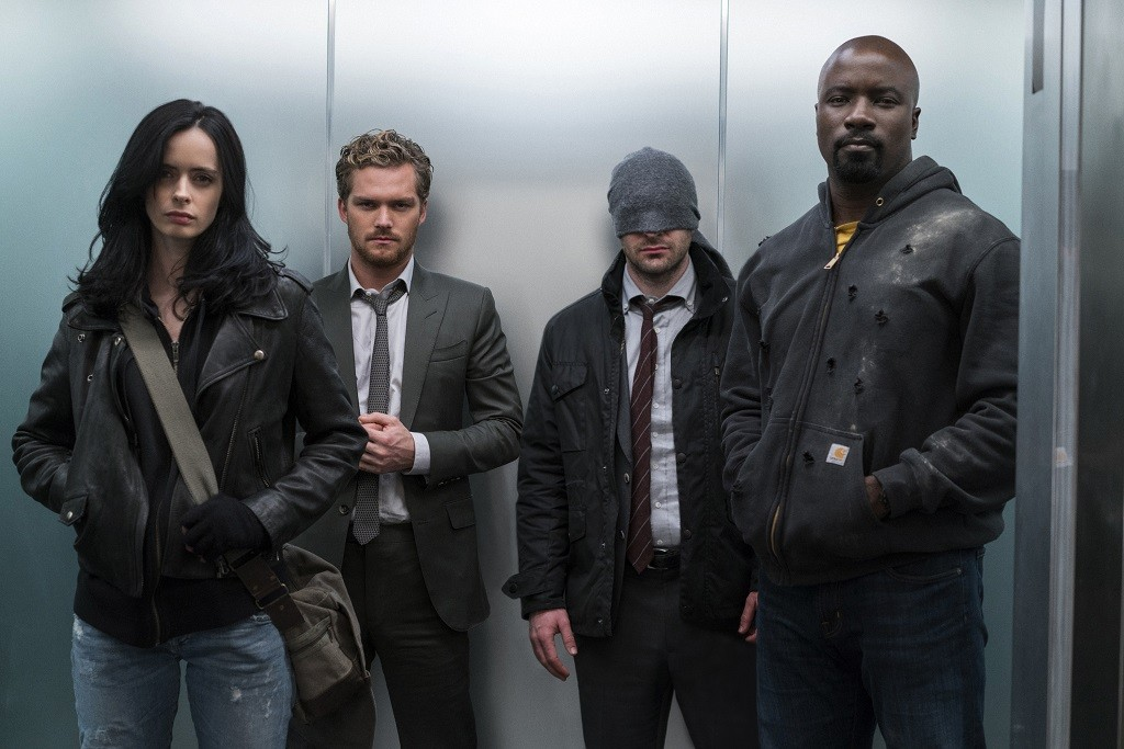 Krysten Ritter, Finn Jones, Charlie Cox, and Mike Coulter in The Defenders standing together in an elevator