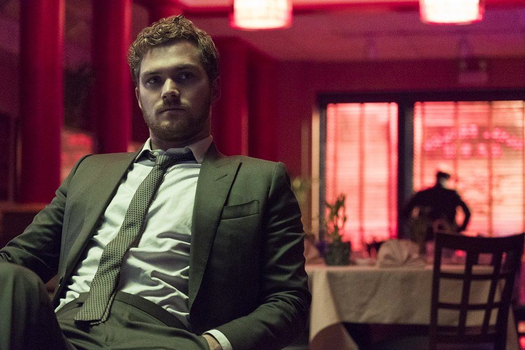 Danny Rand (Iron Fist) sits in a chair in a suit.