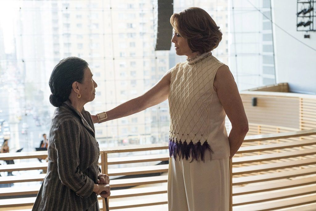 Alexandra rests a hand on the shoulder of Madame Gao while they look at each other.