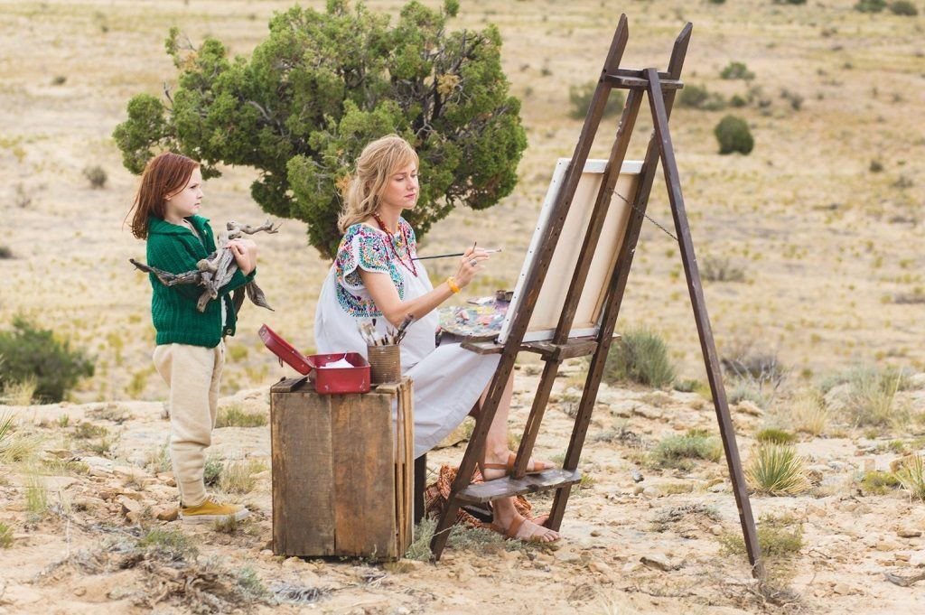 A woman painting on an easel in the desert as a child stands behind her