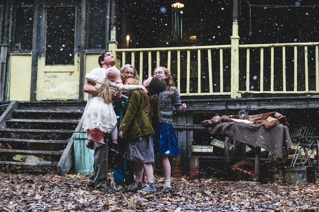 A family stands in a group embrace looking up at the falling snow