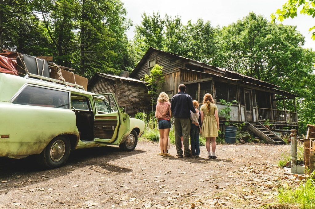 A family stands next to their green car in the woods looking at a rundown cabin