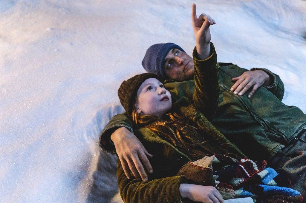 A child and her father lay in the snow as she points up at the sky