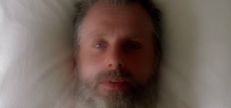 Rick dons a gray beard and looks up while lying in bed
