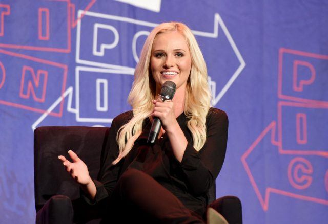 Tomi Lahren speaking into a microphone while sitting on stage.