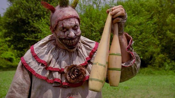 Twisty the Clown holding wooden juggling pins
