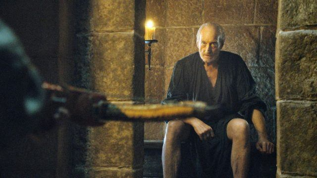 Tywin Lannister sits on a toilet and stares at his son, Tyrion, who is aiming a crossbow at him on 'Game of Thrones.'