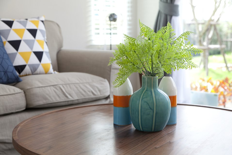 colorful vase with flower on wood table and sofa in livingroom
