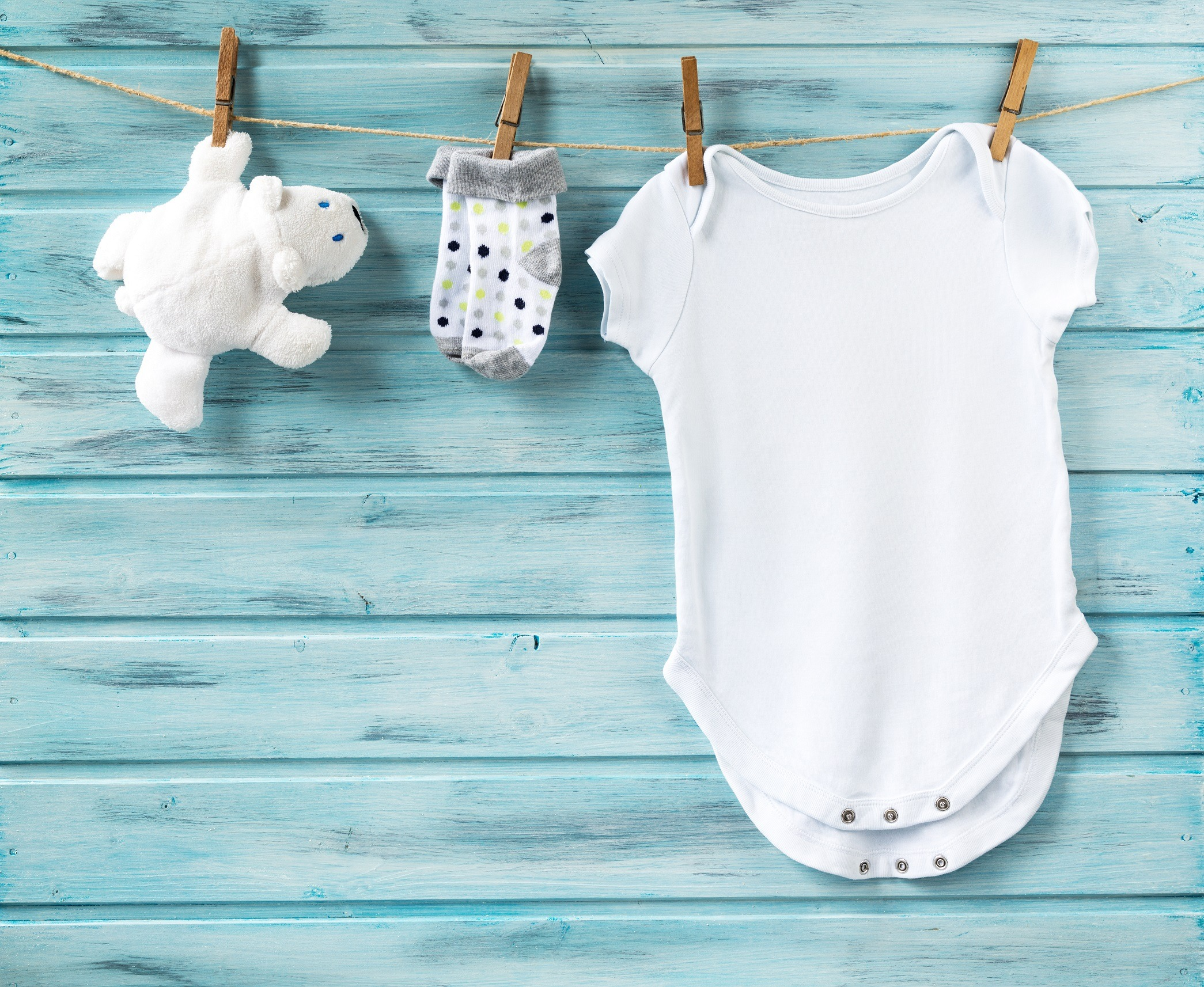 Blue background with white baby onesie and sock