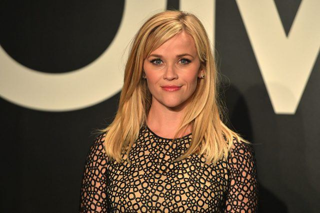 Reese Witherspoon in 2015 wearing a black and nude patterned gown while posing for photos at a red carpet.