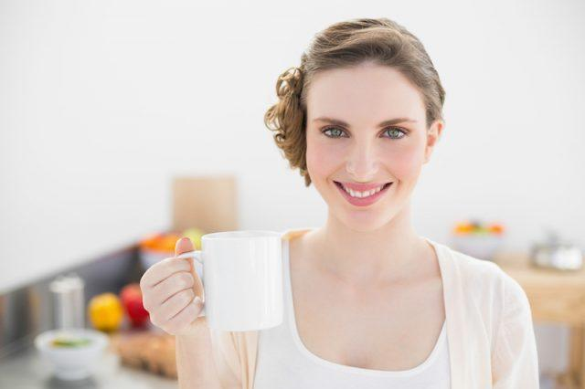 A woman smiles while holding a white mug in her kitchen.