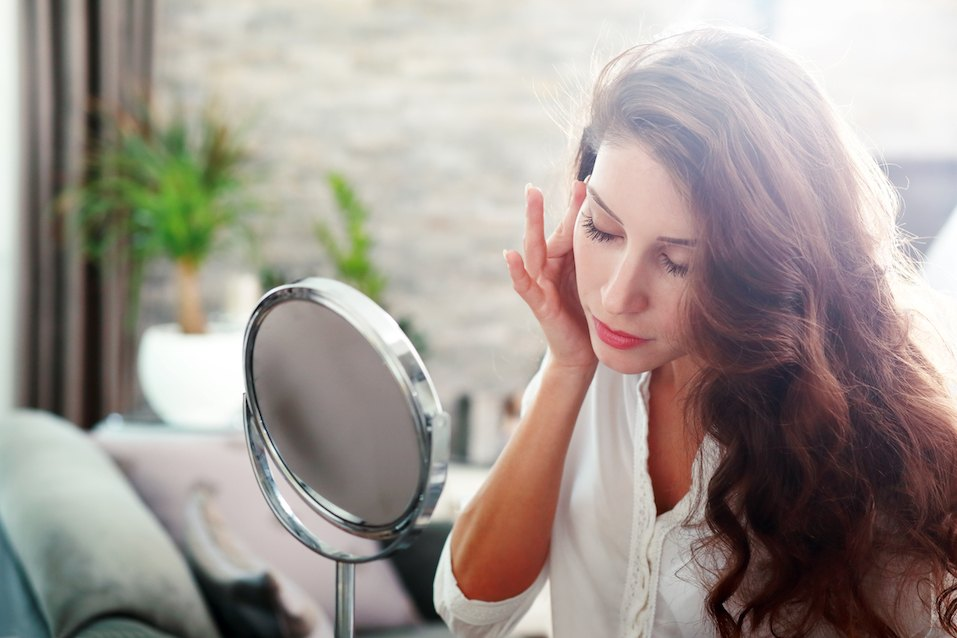 beautiful healthy woman looking in the mirror