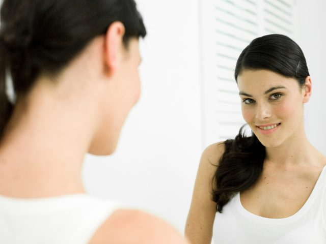 Woman smiling at mirror.