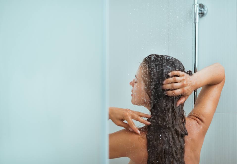 Woman with long hair taking shower