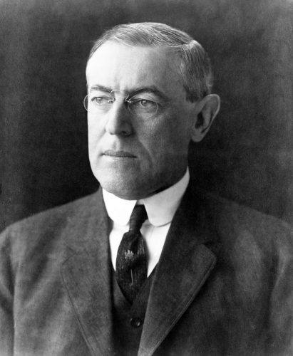 Woodrow Wilson standing in a suit, tie, and glasses.