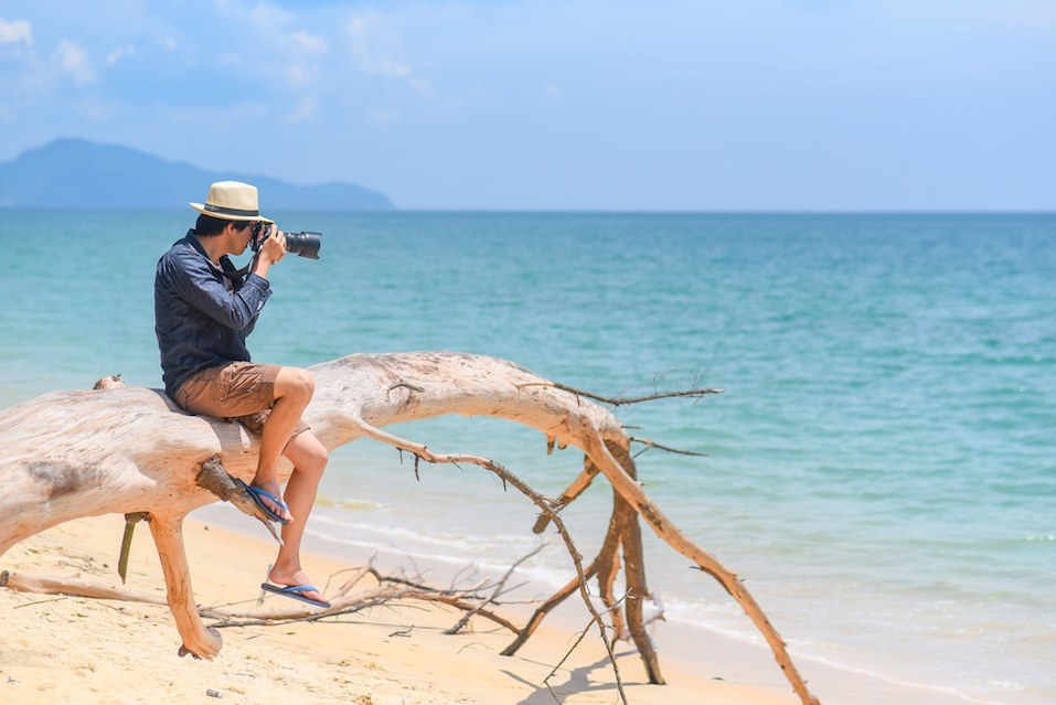 young man photographer take photos on the beach