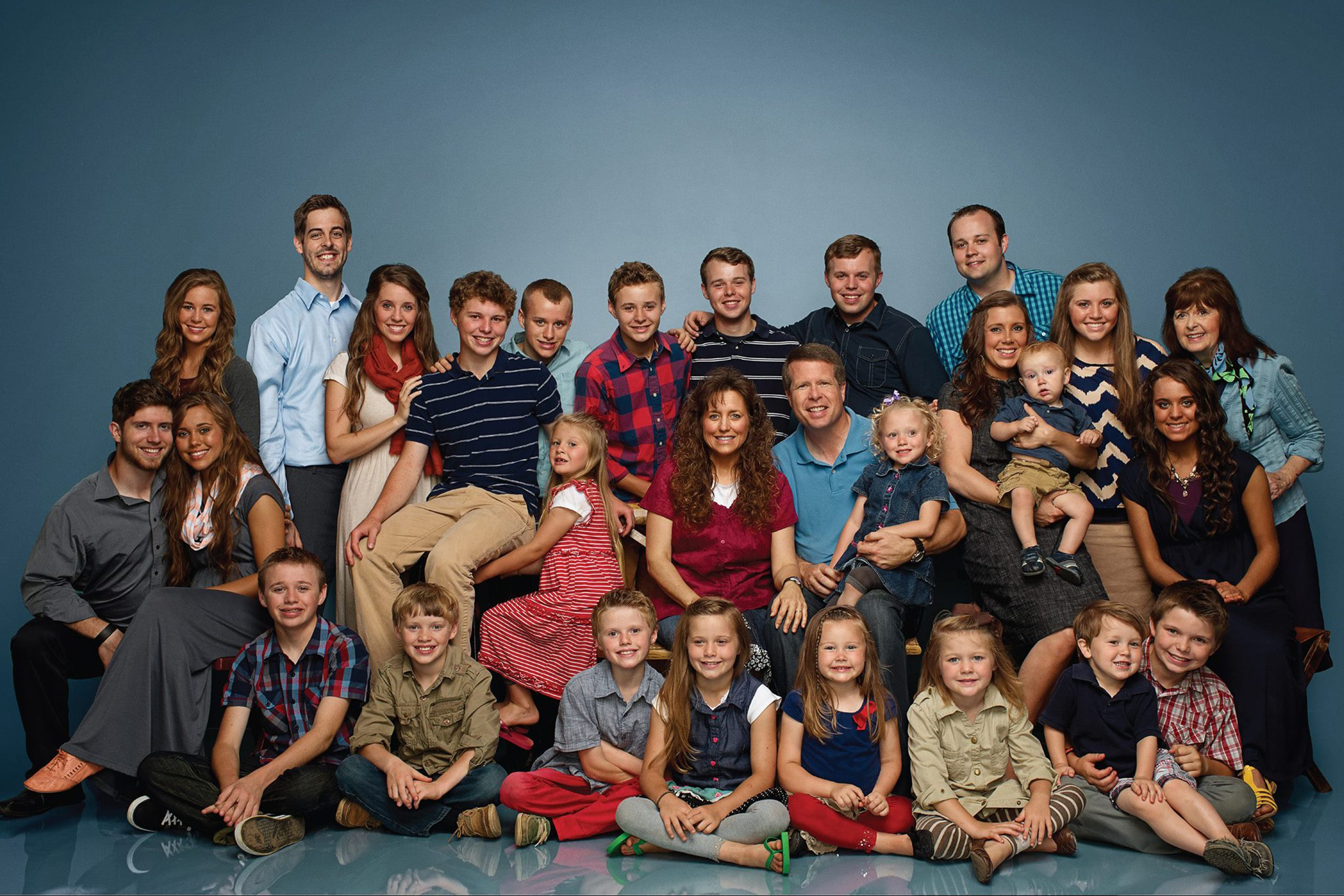 The Duggar Family poses in front of a blue background