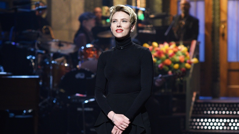 Scarlett Johansson stands on the sNL stage in a black turtleneck with her hands crossed in front of her