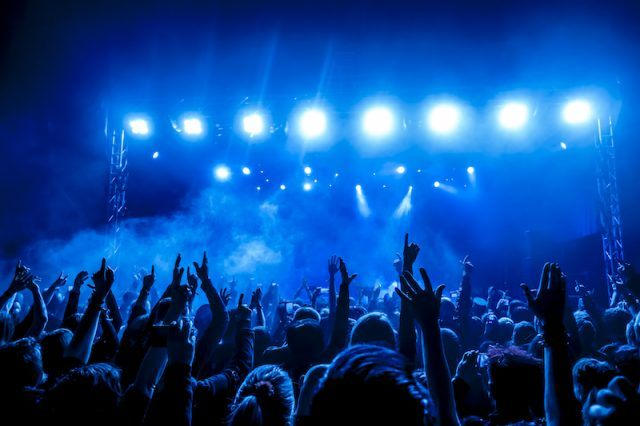 A concert full of a large crowd and bright lights.