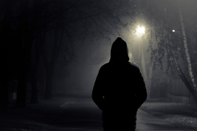 A black hooded figure walks along a dark passageway.