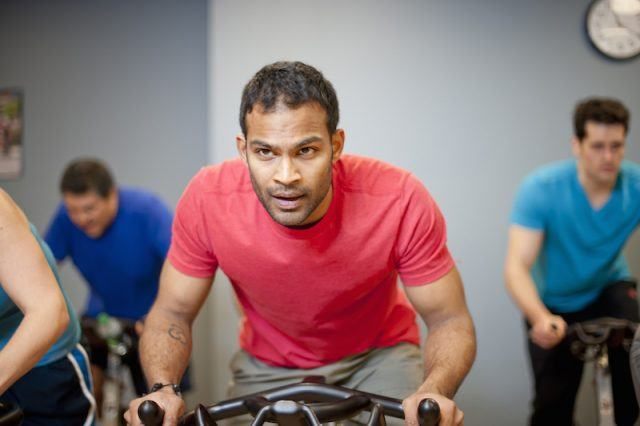 A man is in a spin class with other people.